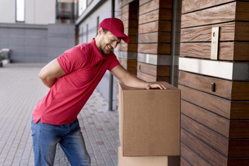 Delivery man suffering from back pain while carrying box - Fruit-Powered