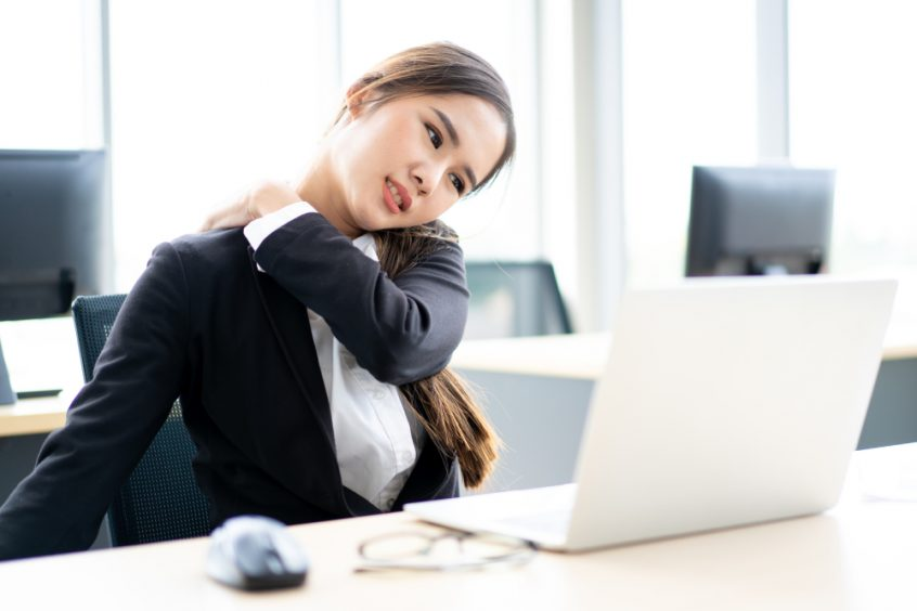 Woman using office computer feeling back pain treatment - Fruit-Powered