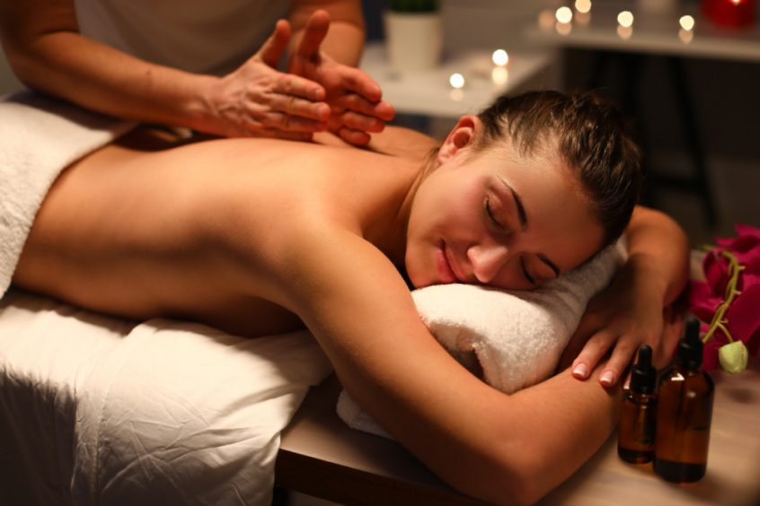 Woman receiving back massage at spa - Fruit-Powered